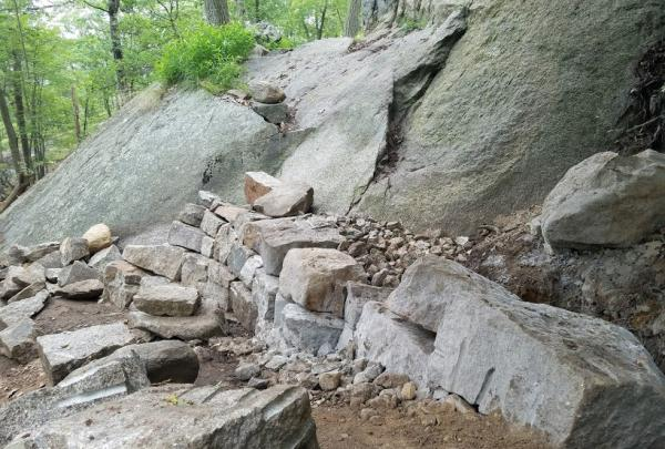 The Megalithic Trail Crew is building a crib wall staircase as part of the Appalachian Trail reroute on Bear Mountain. Photo by Eduardo Gill.