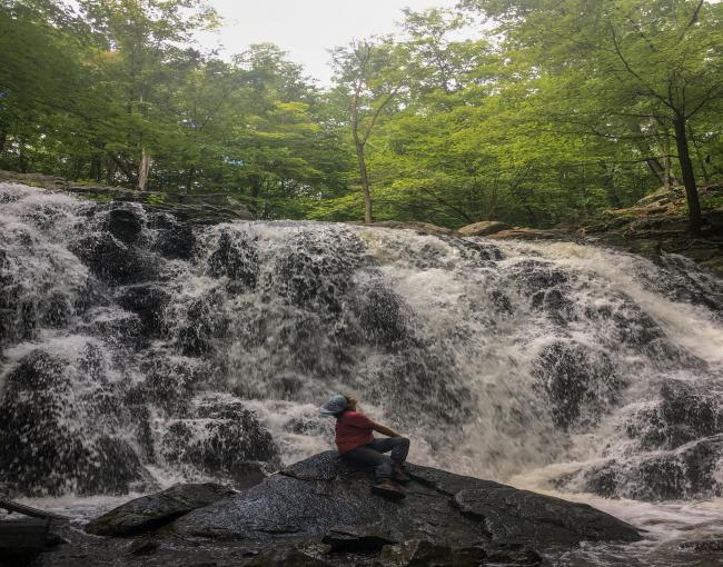Conservation Corps Crew Member Nicole Vargas at the waterfall at Ramapo Valley County Reservation.