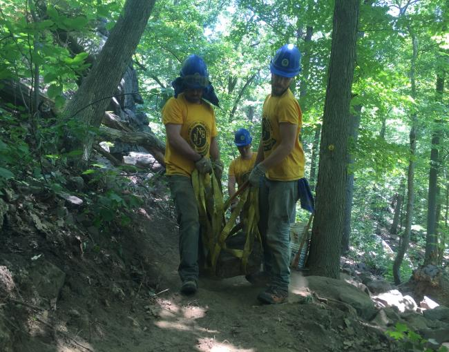 Trail crew members moving a rock.